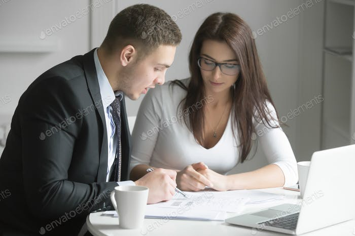 Businessman and businesswoman at office desk, working together w