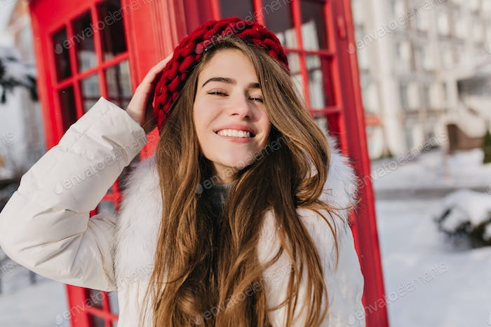 Close-up portrait of joyful long-haired woman in red hat posing in front of phone booth. Outdoor pho