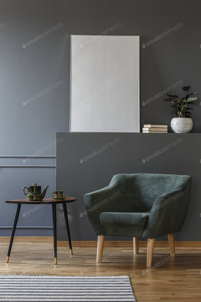 Green armchair next to black table in grey apartment interior wi