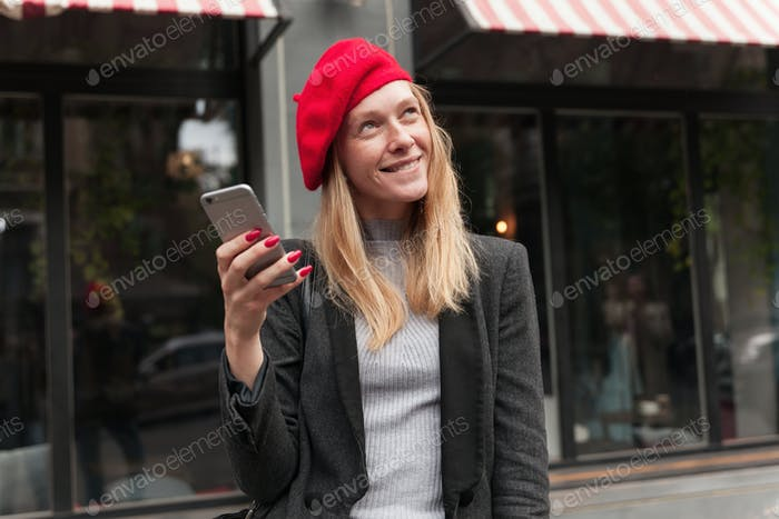Dreamy young attractive blonde female in trendy clothes smiling cunningly while looking upwards