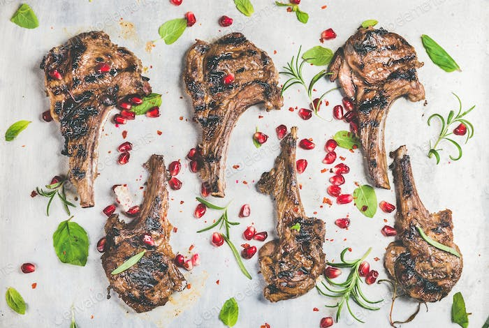 Meat barbecue dinner with grilled lamb ribs and pomegranate, herbs