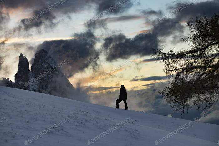 Lonely traveller in Dolomite mountains at winter.