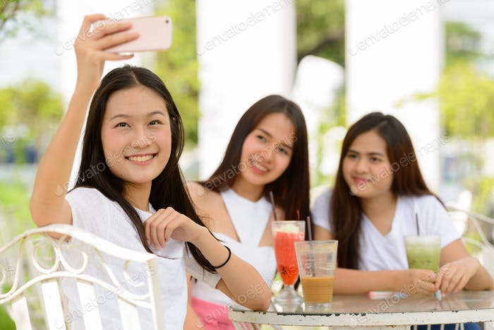Three happy young Asian women as friends taking selfie together at the coffee shop outdoors