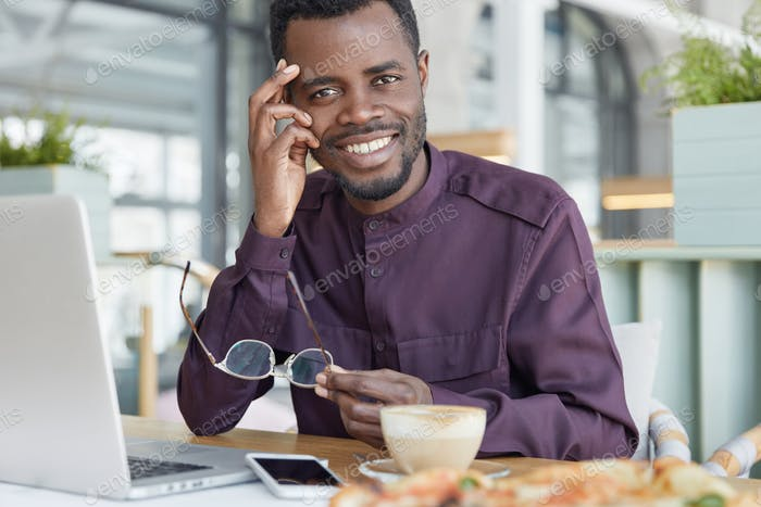 Happy dark skinned male freelancer uses modern electronic gadgets for remote work, sits against cozy