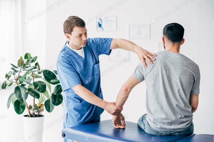 Physiotherapist massaging arm of patient on massage table in hospital