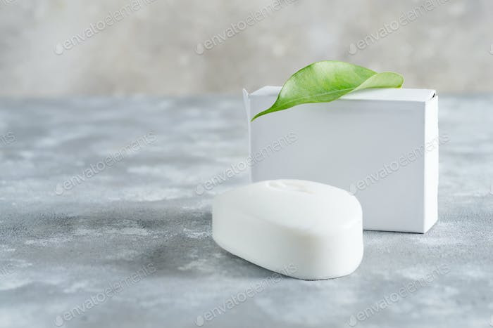 White soap for hand with leaf at stone background. Mock up for logo and text