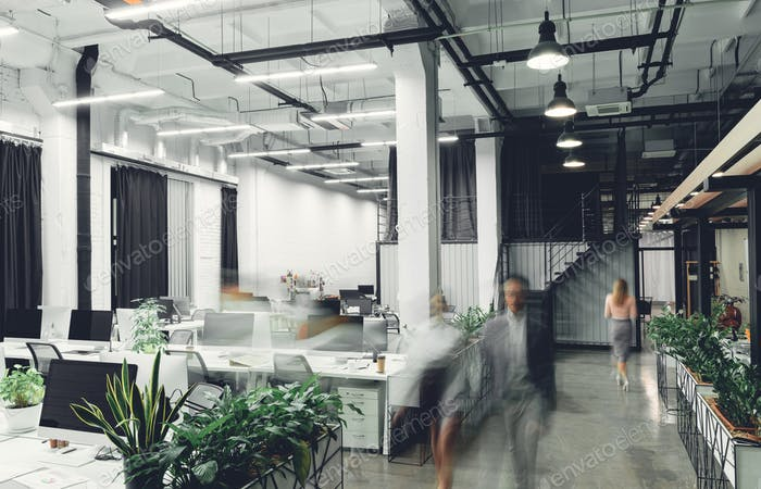 modern office interior with blurred businesspeople in motion
