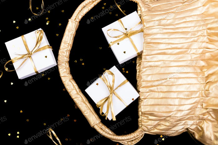 White gift boxes with gold ribbon pop