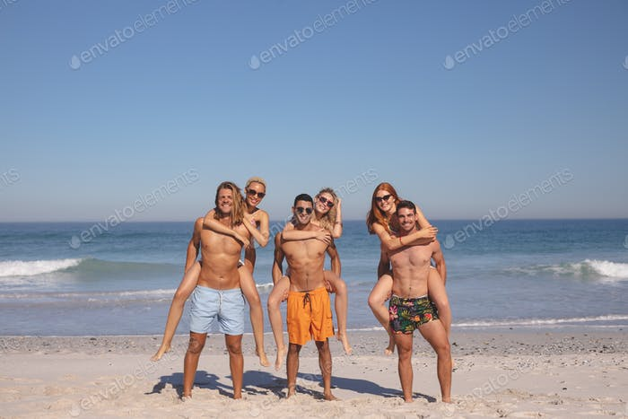 Front view of young diverse male friends giving piggyback ride to female friends on the beach