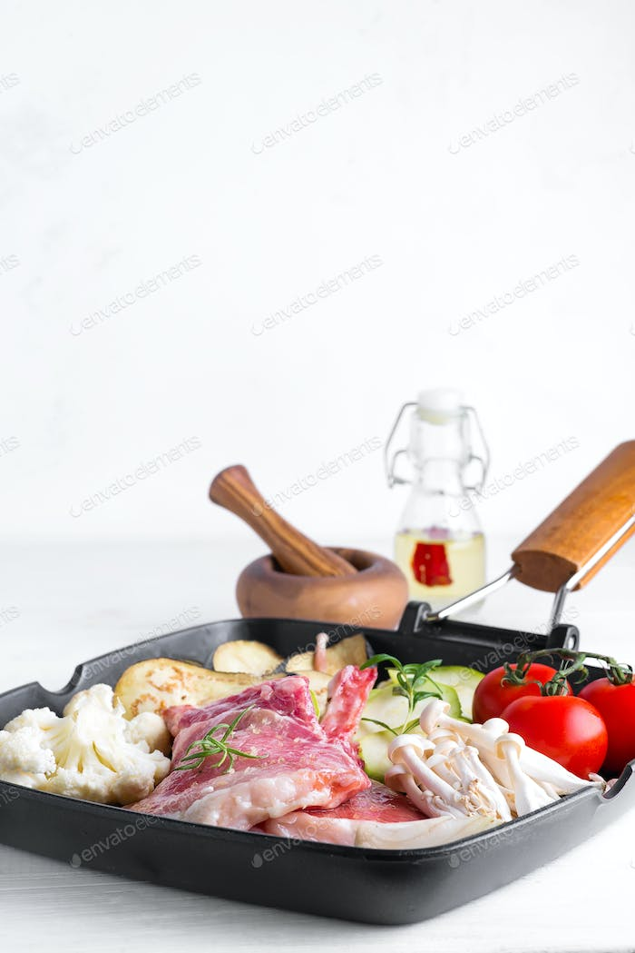 Raw lamb ribs marinating with fresh vegetables in a grill pan on a white stone background, copy