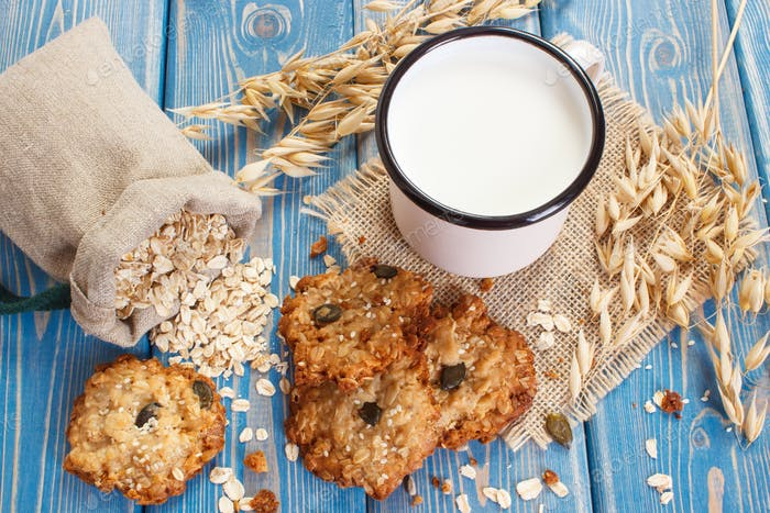 Crusty oatmeal cookies, ingredients for baking and ears of oat, healthy dessert concept