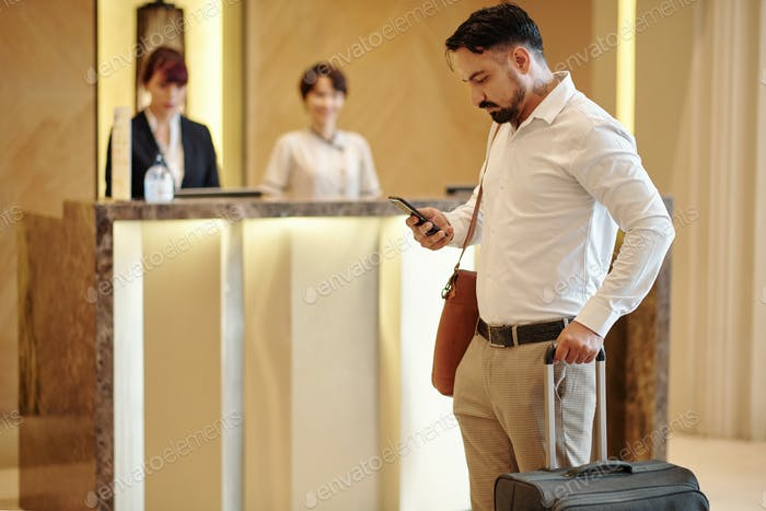 Hotel guest checking phone