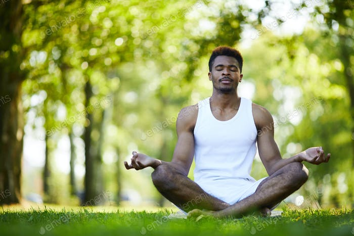 Relaxed black man meditating alone in park
