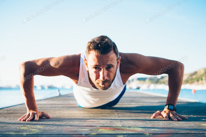 Healthy fit man exercising push ups