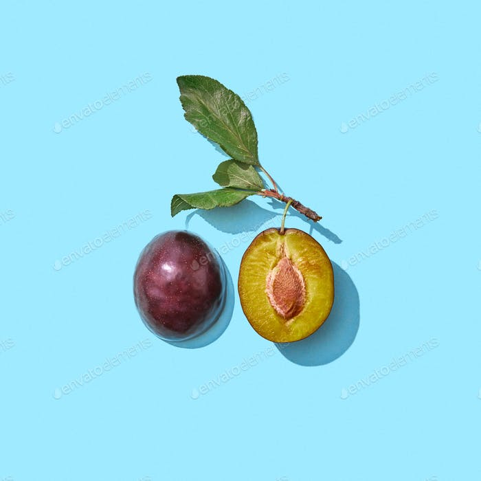 Two juicy half plum with green leaves presented on a blue background with copy space. Healthy food
