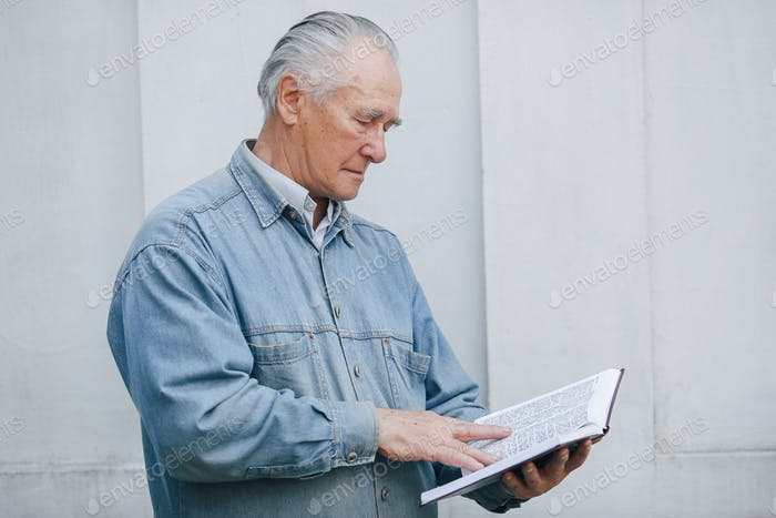 Elegant old man standing on gray background with a book