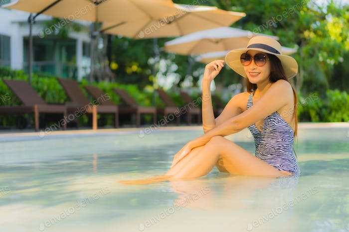 Beautiful young asian women happy smile relax around outdoor swimming pool