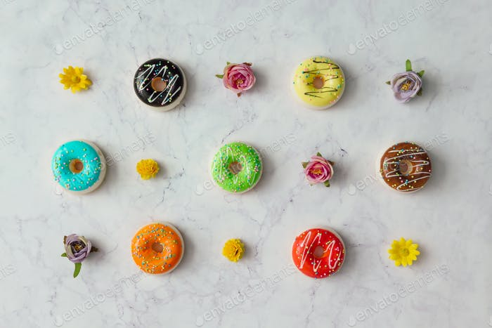 Creative arrangement of colorful donuts and flowers on marble background.