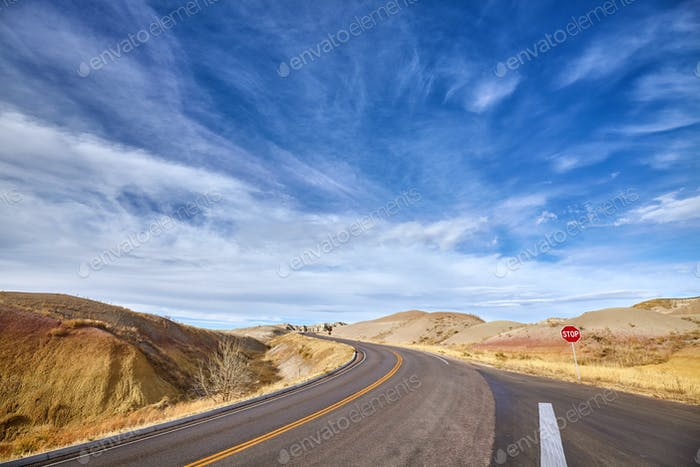 Beautiful cloudscape and highway with a stop sign.