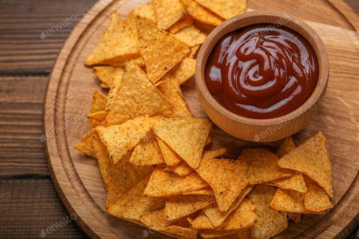 Mexican nachos chips with spicy tomato sauce on wooden backgroun