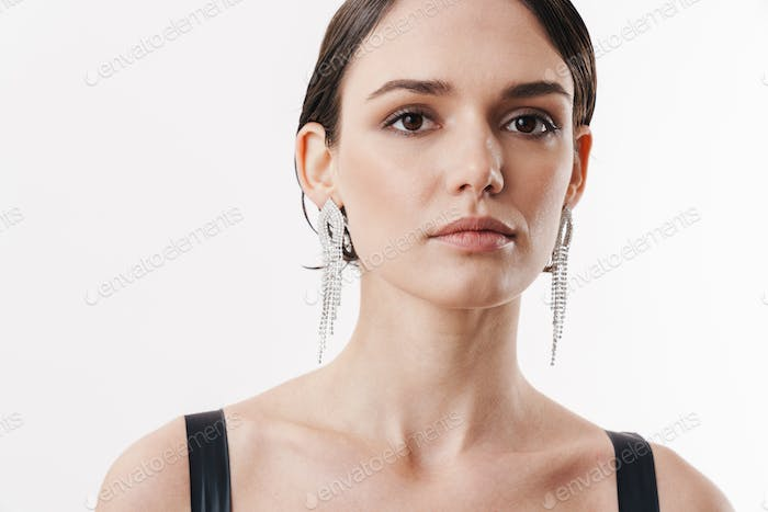 Image of pretty brunette young woman wearing dress looking at camera