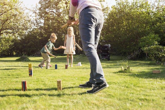 Children (4-5, 8-9) playing Kubb
