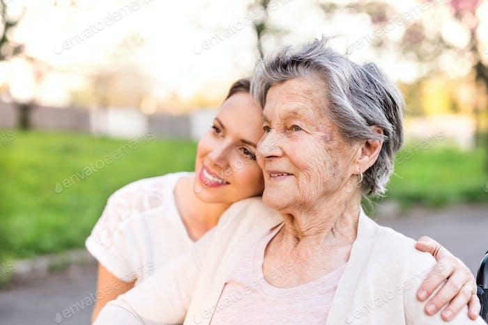 Elderly grandmother and granddaughter hugging in spring nature.