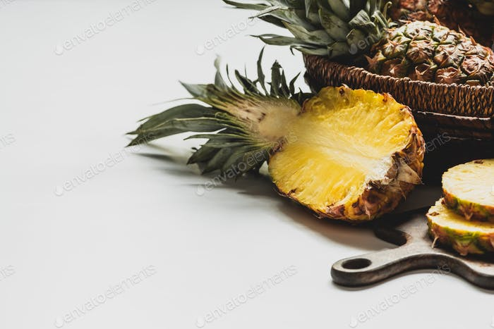 Fresh Cut Delicious Ananas auf Holz-Schneidebrett und im Korb auf weißem Hintergrund