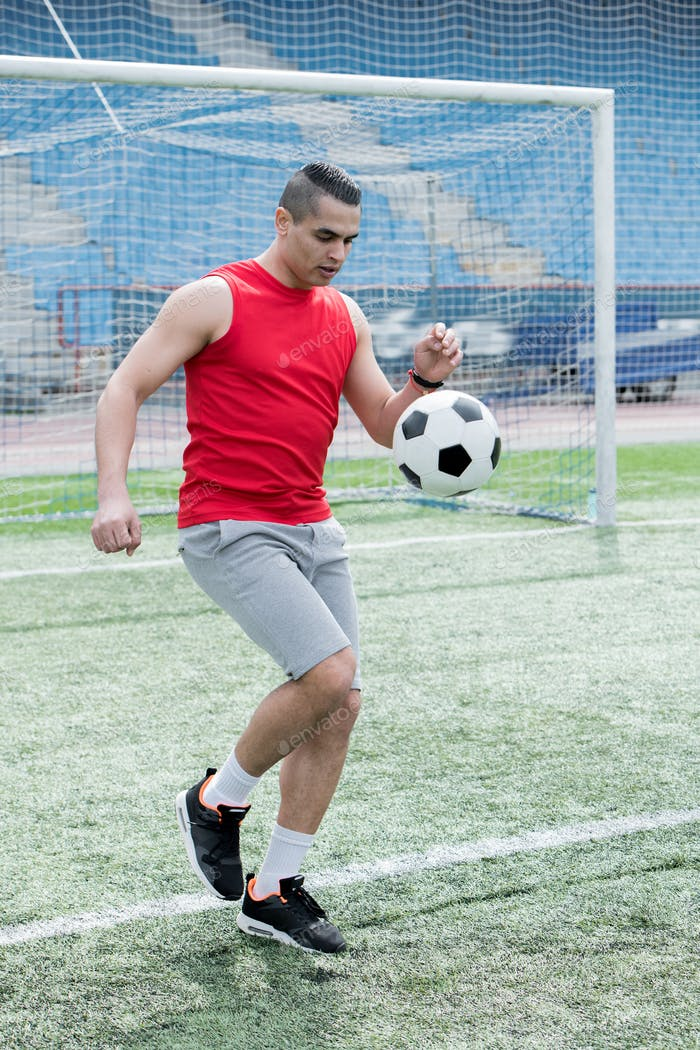 Handsome Man Playing Football in Stadium