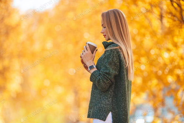 Fall concept - beautiful woman drinking coffee in autumn park