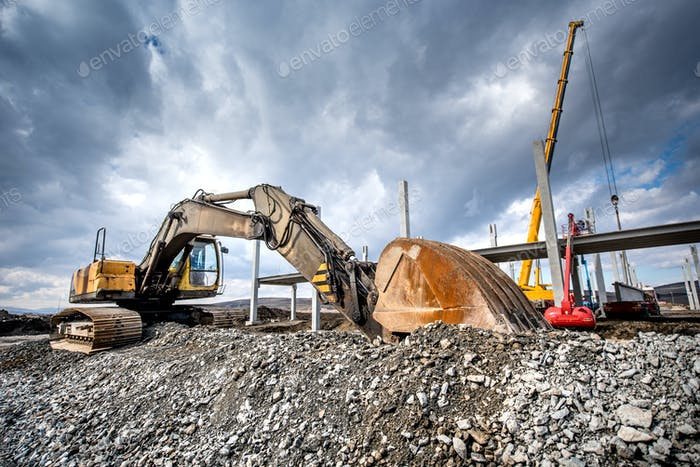 Heavy duty industrial excavator loading gravel on construction site. Details of building site