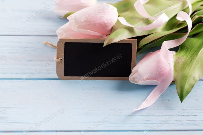 Congratulation holiday card with fresh tender pink tulips flower and chalkboard for message on a