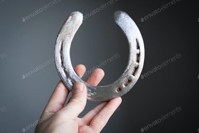 man holding a steel polished horshoe