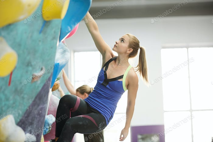 Fit blonde woman with ponytail holding by one of small rocks on climbing wall