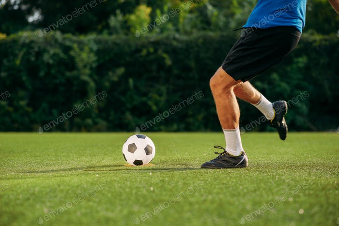 Male soccer player hits the ball on the field