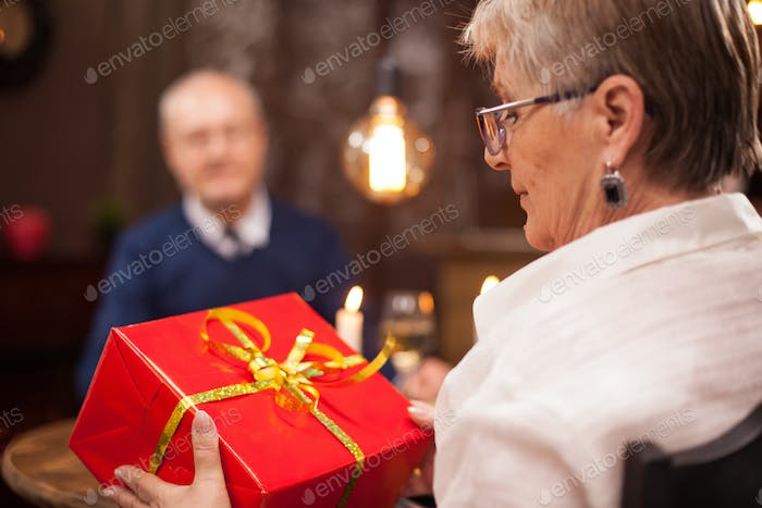 Kind old lady look at the gift that her husband gave her while having dinner