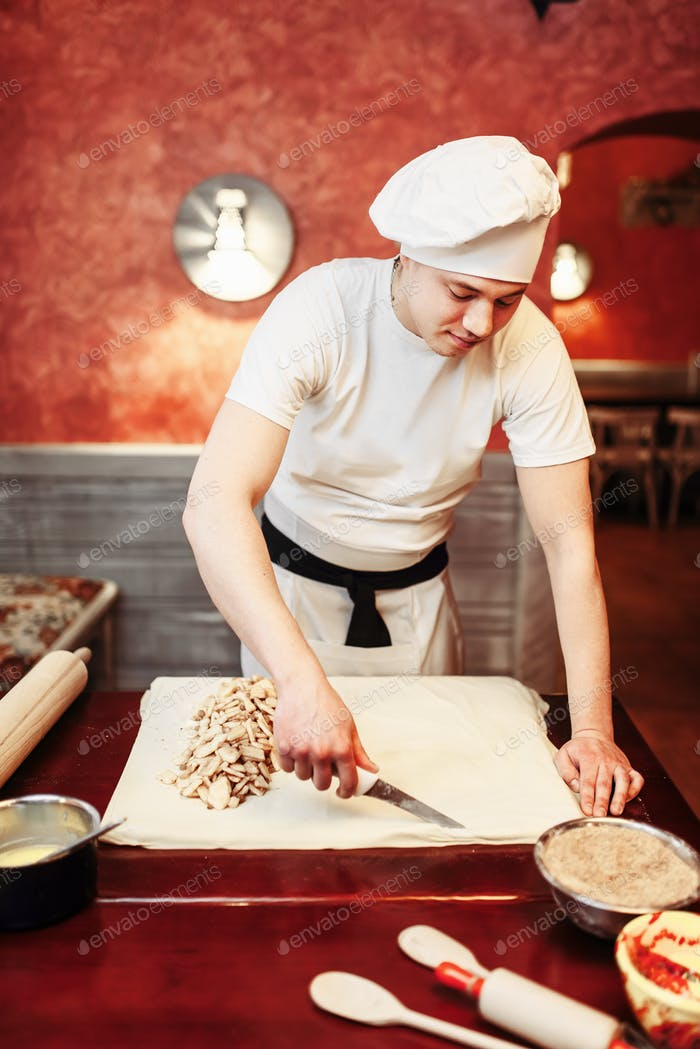 Male chef prepares apple strudel