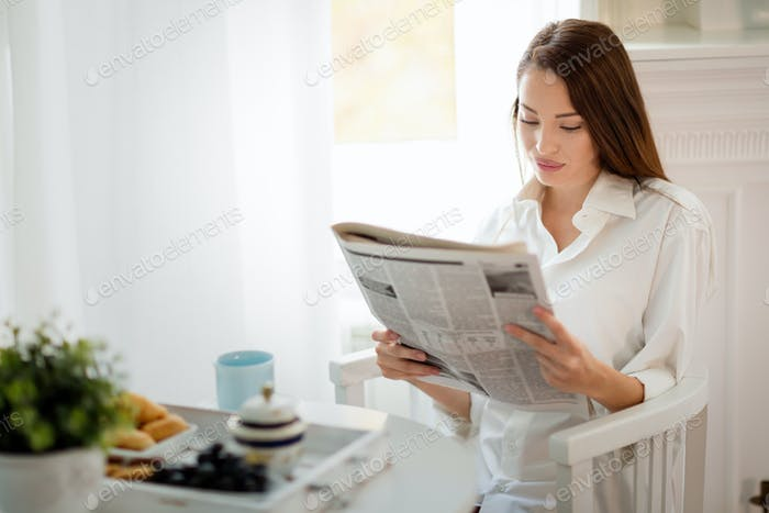 Young beautiful woman reading magazine at table