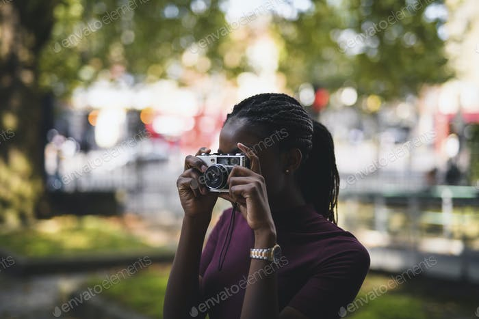 Woman taking photos with a vintage film camera