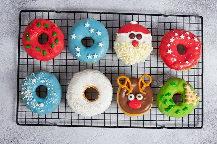 Set of Christmas donuts on baking rack on gray stone background.