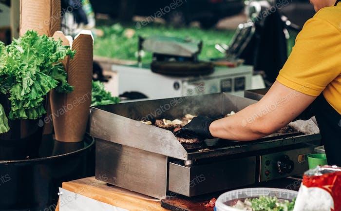 Man macht Burger, Braten von Fleisch und Gemüse auf dem Grill