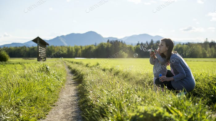 Young mother kneeling down to her child blowing soap bubbles tog