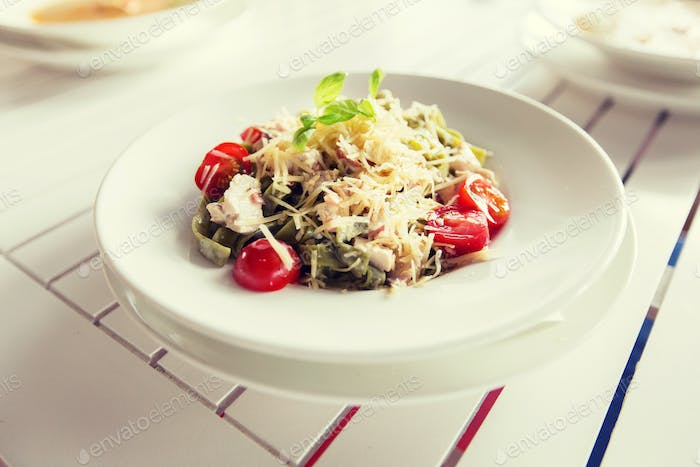 close up of pasta with tomato and cheese on plate