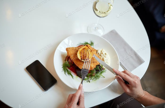 woman with smartphone eating salad at restaurant