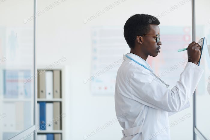 Young African-American Doctor Writing on Glass Wall