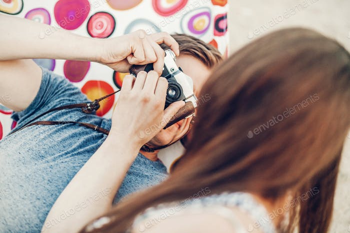 Handsome man taking picture of a beautiful brunette girl
