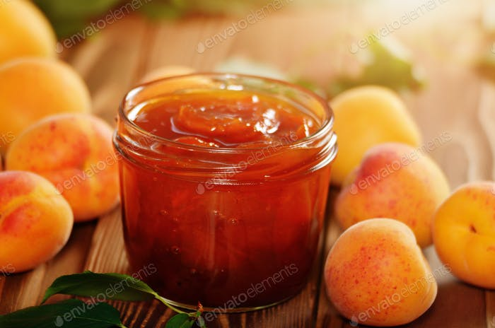 Glass Jar of Apricot jam on wooden table with ripe apricots asid