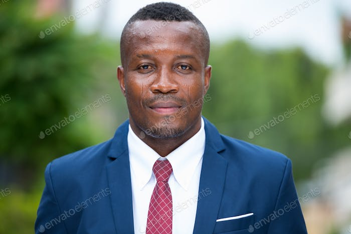 Young African businessman wearing blue suit outdoors