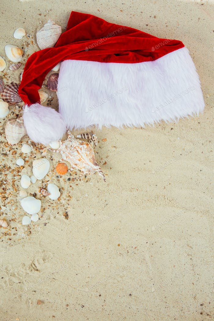 Christmas hat on the beach. Santa the sand near shells.New year vacation.