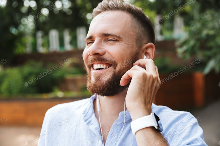 Young bearded man outdoors listening music